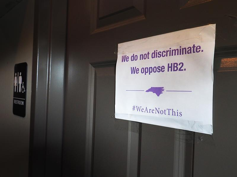 """A unisex sign and the """"We Are Not This"""" slogan are outside a bathroom at Bull McCabe's Irish Pub on May 10 in Durham, N.C."""