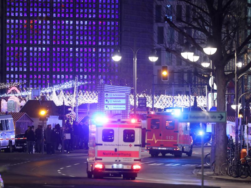 An ambulance and rescue workers arrive on the scene after someone drove a truck through a Christmas market in Berlin on Monday.
