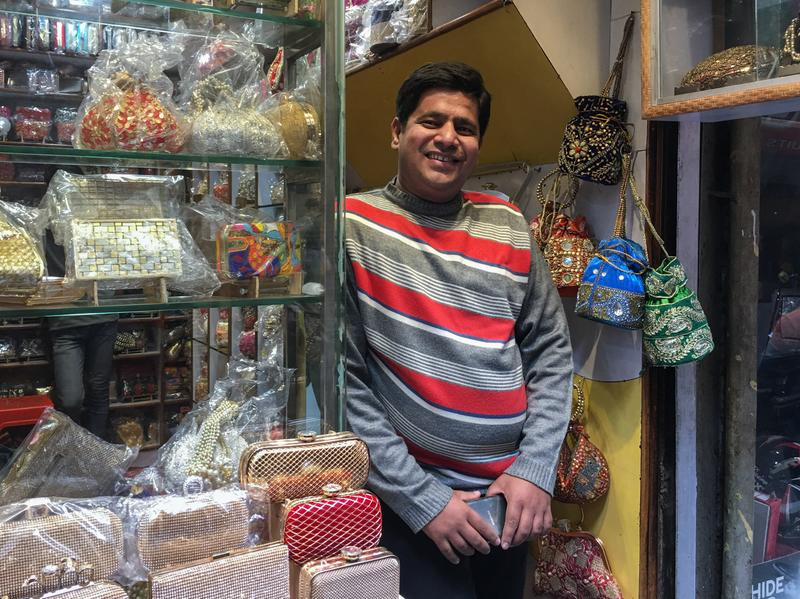 """In the Old City of New Delhi, Asim Husain stands in his shop, where he sells hand-stitched purses. He says sales normally conducted in cash are down nearly 90 percent and his attempts to go """"cashless"""" with credit cards or other e-wallet schemes have not met with great success. """"The connectivity is very poor,"""" Husain says, referring to the internet."""
