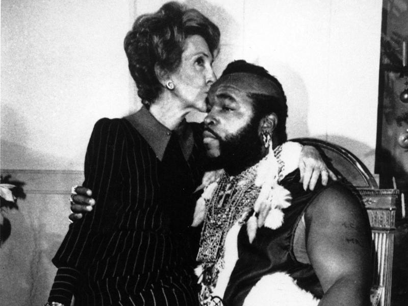 First lady Nancy Reagan sits on the knee of Mr. T, dressed as Santa Claus, and gives him a peck on the head, as he joined her for a preview of the White House Christmas decor in 1983.