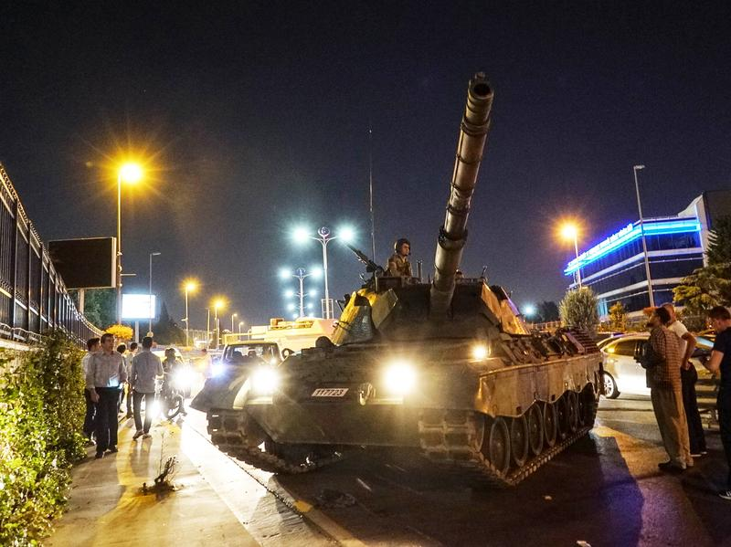 People gather near a Turkish army tank in Istanbul on July 16, after a group within Turkey's military attempted a coup. Since then, more than 100,000 people been detained, fired or suspended from their jobs on suspicion of sympathizing with or aiding the coup attempt.