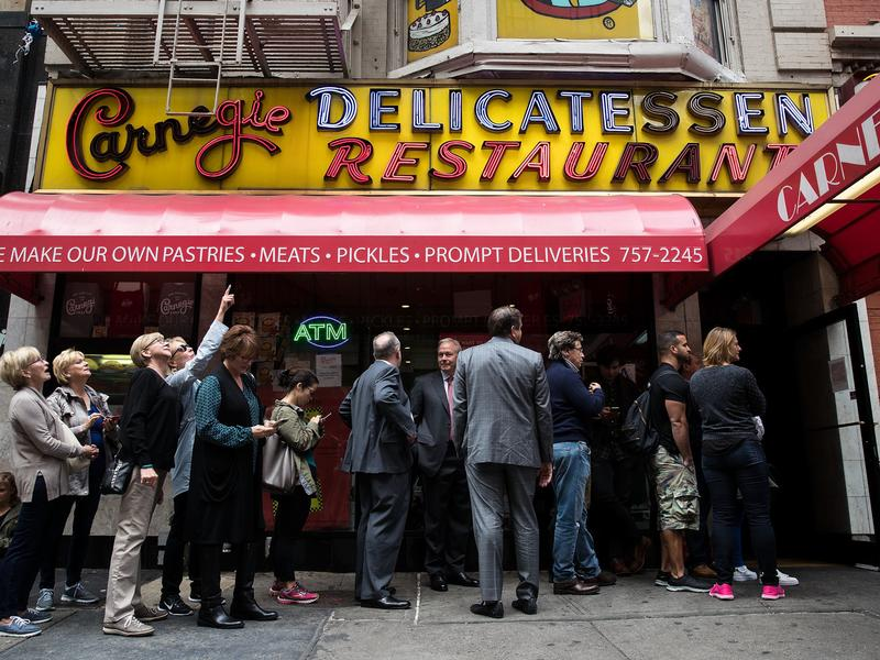 Customers wait in line outside for a table at the Carnegie Deli.