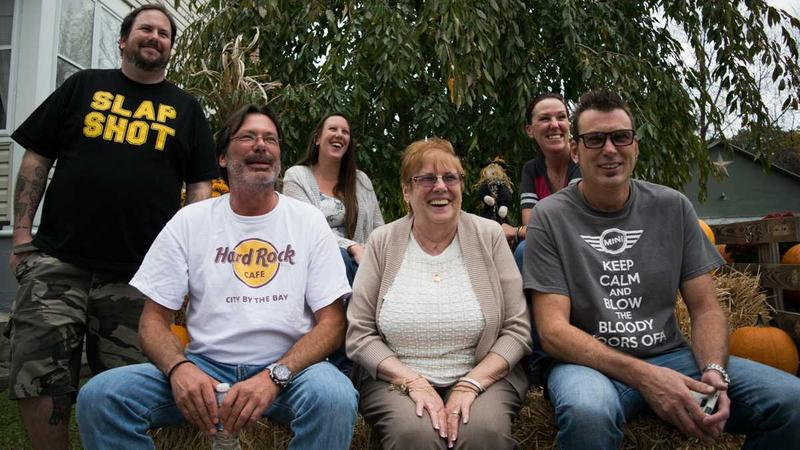Front row: Scott Winter, left, sits next to his biological mom, Nancy Oakes Dewitt, and his older brother, Keith Murphy. In the second row, Charles Murphy, Jeannette Murphy and Lynnae DePaolo. (Paige Pfleger/WHYY)