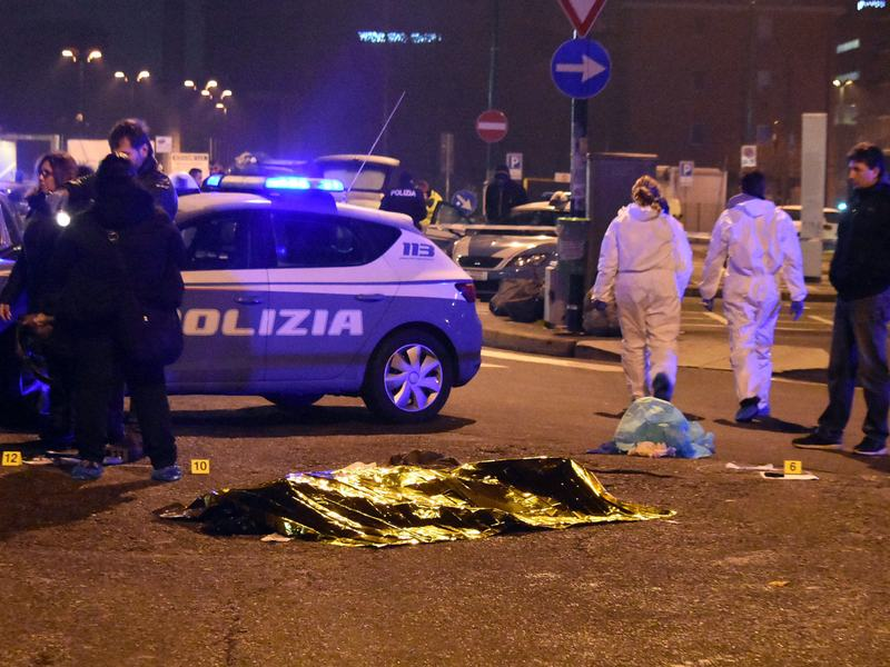 """A body is covered with a thermal blanket after a shootout between Italian police and a man near a train station in Milan's Sesto San Giovanni neighborhood early Friday. Italy's interior minister said the man killed is """"without a shadow of doubt"""" Anis Amri, the suspect in the Berlin Christmas market attack."""