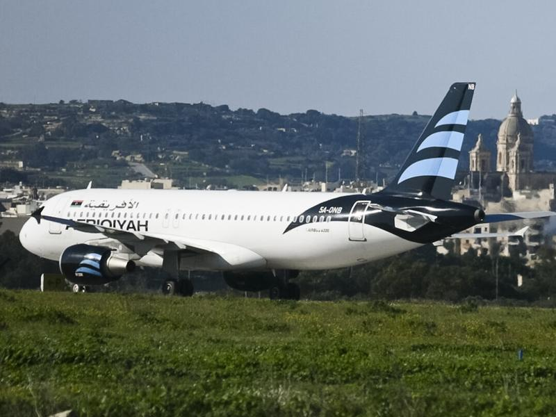 An Afriqiyah Airways plane from Libya sits on the tarmac in Malta on Friday. Malta's state television said two hijackers who diverted a Libyan commercial plane to the Mediterranean island nation had threatened to blow it up.