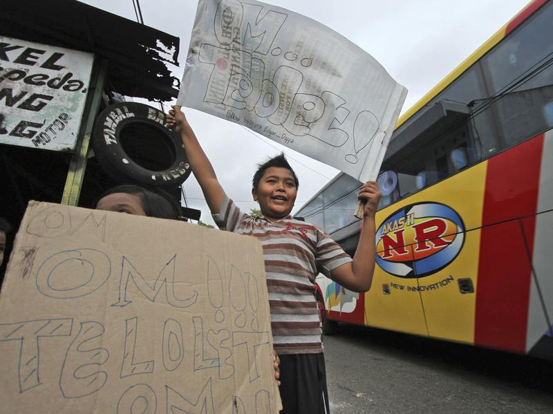 Children on the side of a road in Solo in Indonesia's Central Java province ask passing bus drivers to honk their horns on Friday. Videos of children with signs like these have recently gone viral.