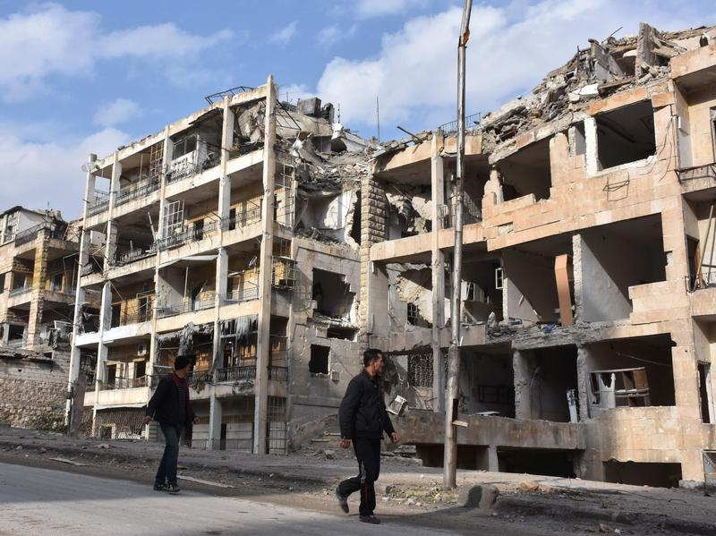 Syrians walk past destroyed buildings in the former rebel-held Ansari district in Aleppo on Friday after Syrian government forces retook control of the whole embattled city.