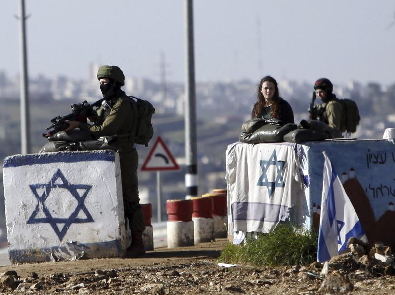 The U.N. Security Council has condemned Israel's construction of settlements, with Ambassador Samantha Power saying the project hurts Israel's security. In this photo from March, soldiers guard the Gush Etzion junction near a cluster of settlements in the West Bank.