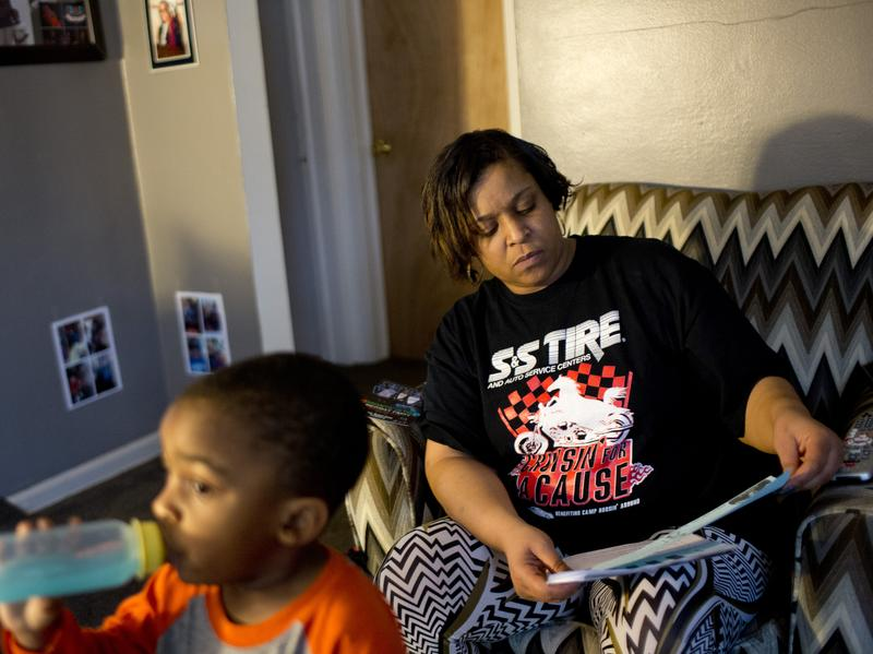 Jeneyah McDonald looks over homework her oldest son Justice, 6, brought home from school while her youngest son Josiah, 2, drinks Kool-Aid from a bottle at their home in Flint, Mich., in February.