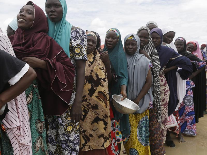 Women displaced by Islamist extremists wait for food to be handed out to them at the Bakassi camp in Maiduguri, Nigeria. Boko Haram's uprising has killed more than 20,000 people, and displaced some 2.3 million more.