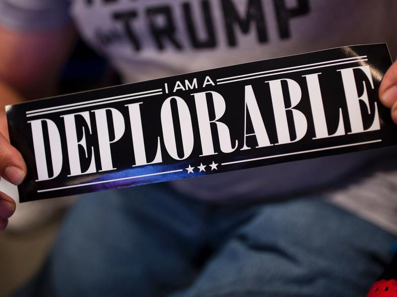 """A supporter of Republican presidential candidate Donald Trump shows a bumper sticker reading """"I am a Deplorable"""" at Mohegan Sun Arena in Wilkes-Barre, Pa., on Oct. 10. The term references comments by Hillary Clinton that suggest some Trump supporters are """"deplorables."""""""