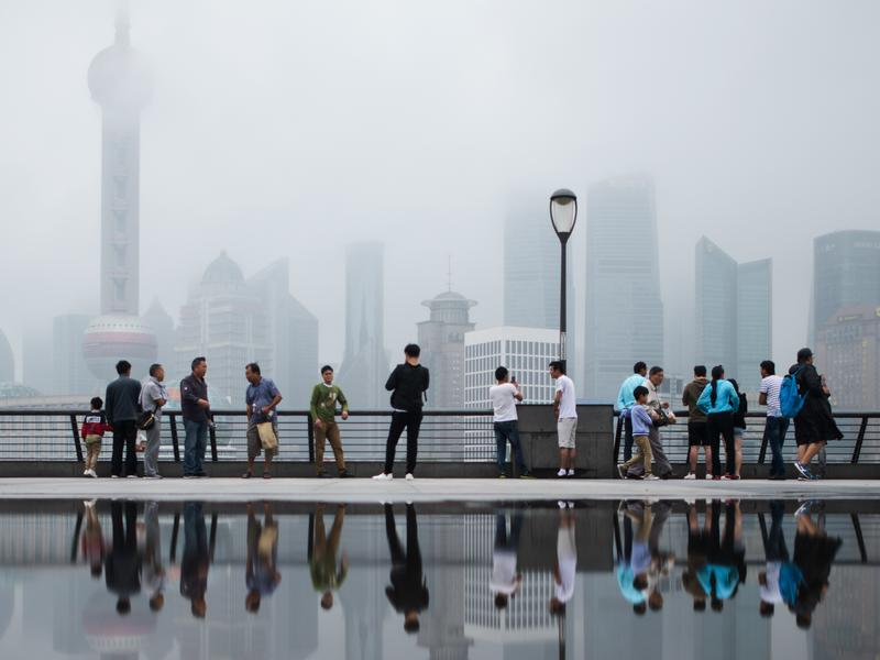 """People in Shanghai overlook the financial district in June 2016. The Shanghai city government recently released an app that produces a """"public credit score"""" for residents. A good score can lead to discounts, but a bad score can cause problems."""