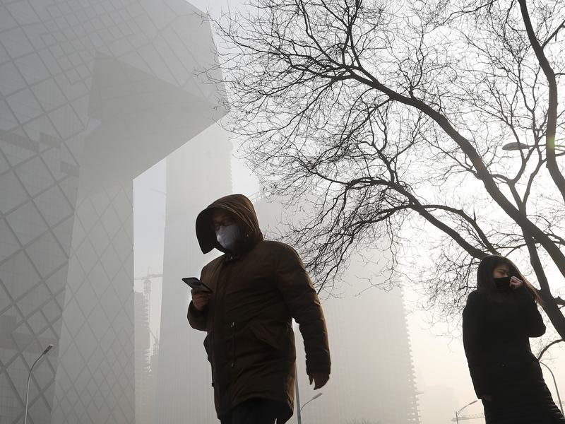 People wearing protective masks walk near the iconic headquarters of Chinese state broadcaster Central China Television in Beijing, which has been blanketed by heavy smog.