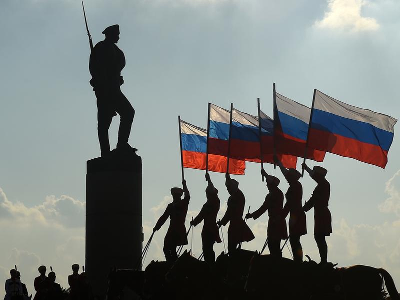 Russians hold their national flag next to a bronze statue of a soldier in Moscow on Aug. 22, 2016, during celebrations of the National Flag Day. U.S. intelligence agencies say Russia is engaged in a widespread disinformation campaign that targets the U.S. and many other countries.