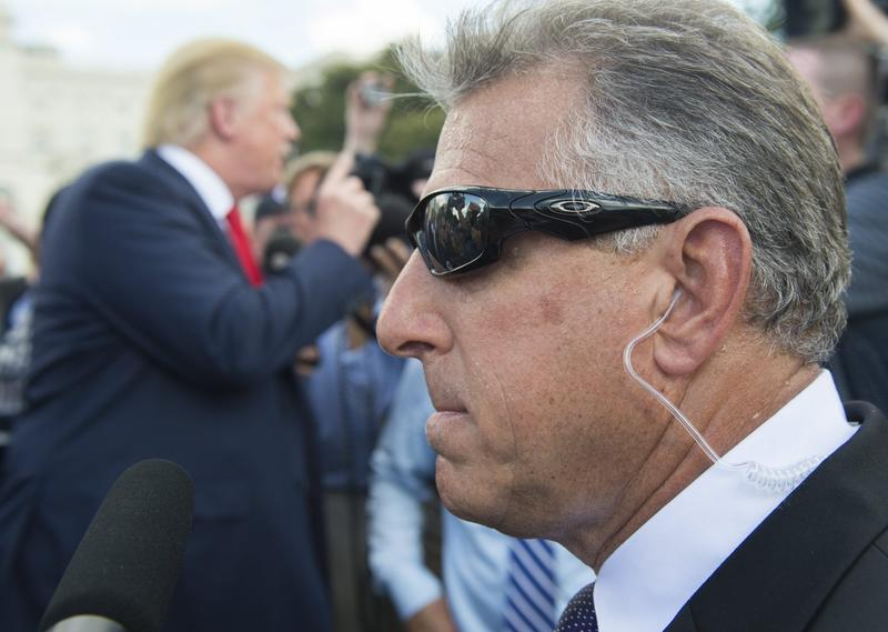 A member of Donald Trump's private security team stands watch as Trump speaks with reporters on the campaign trail in Washington, D.C., in September 2015. (Saul Loeb/AFP/Getty Images)