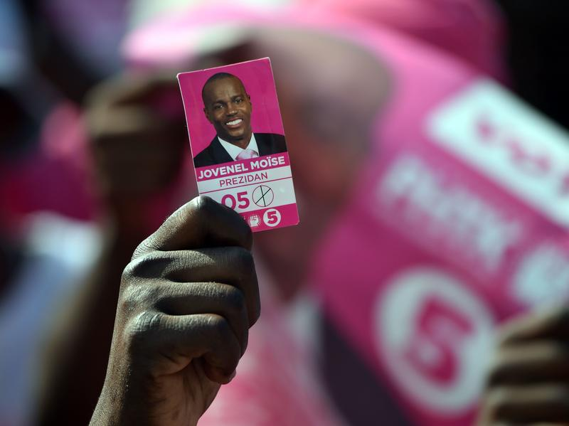 A protester holds a photo of presidential candidate Jovenel Moise near the headquarters of the Provisional Electoral Council in Port-au-Prince last April, as demonstrators demanded that elections be held. Haiti's tortuous election process dragged on for more than 14 months before Moise was declared the victor.