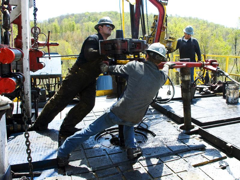 Workers move equipment at a natural gas well site near Burlington, Pa., in 2010. A federal report said Thursday natural gas production is on track to make the U.S. a net exporter of energy by about 2030.