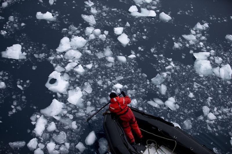In this Jan. 22, 2015 Manuel Fuentes, a Chilean Navy member, paddles through glacial melting in Antarctica. (Natacha Pisarenko/AP)