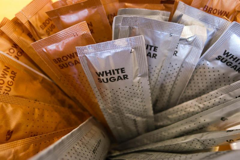 A collection of brown and white sugar packets. (James Brooks/Flickr)
