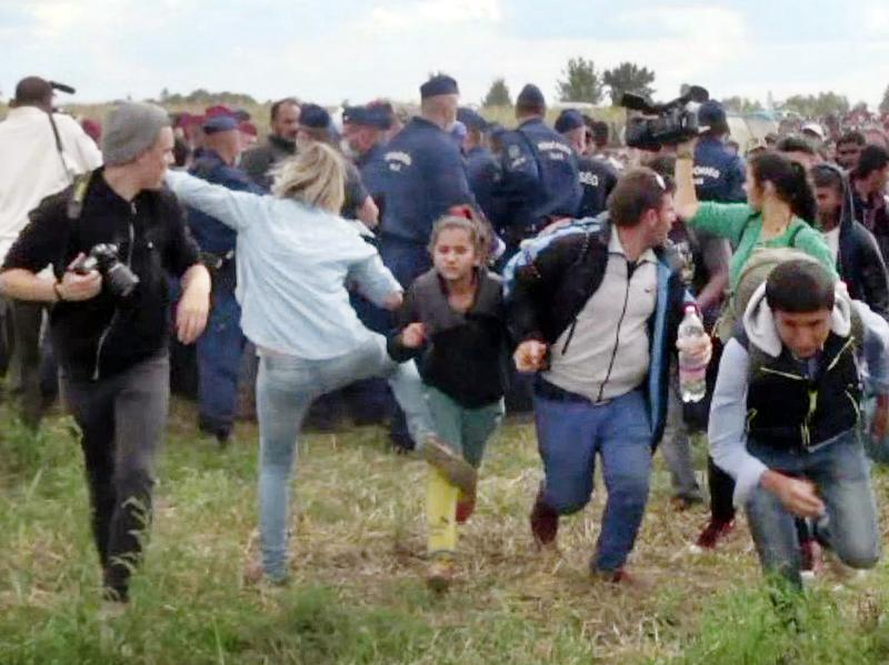A screen grab shows a Hungarian TV camerawoman kicking a child running with other migrants from a police line during disturbances at Roszke, southern Hungary, in 2015. After the footage appeared, the camerawomen was fired. She has been sentenced to three years' probation.
