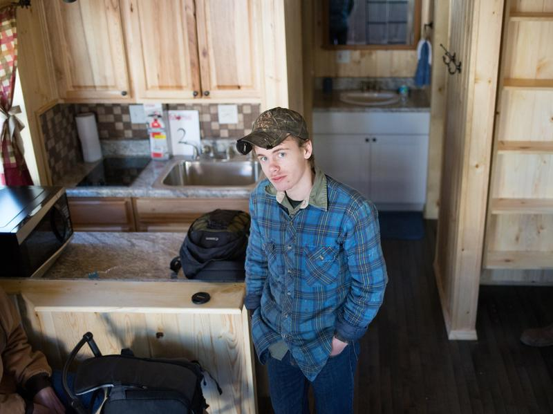 A student stands in one of the tiny houses created for flood victims in West Virginia. The homes, built by high school students, are fewer than 500 square feet.