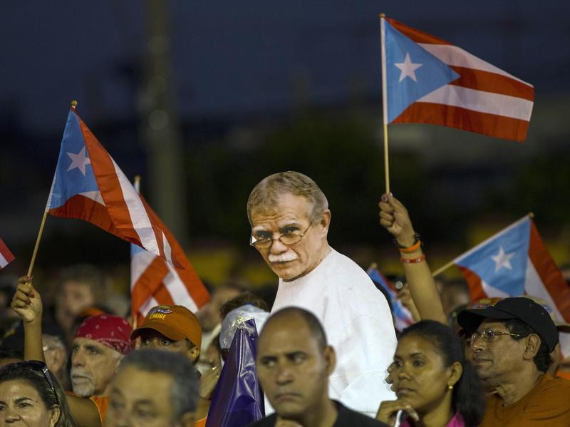 Puerto Rican activists show a picture of independence fighter Oscar López Rivera, center, jailed in the United States, during an event celebrating Revolution Day in Santiago, Cuba, on July 26, 2015.