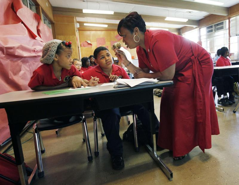 Trenise Duvernay talks to Miracle Lee, left, and Danny Dinet, center, as she teaches fourth grade math class at the Alice M. Harte Charter School in New Orleans in April 2010. (Gerald Herbert/AP)