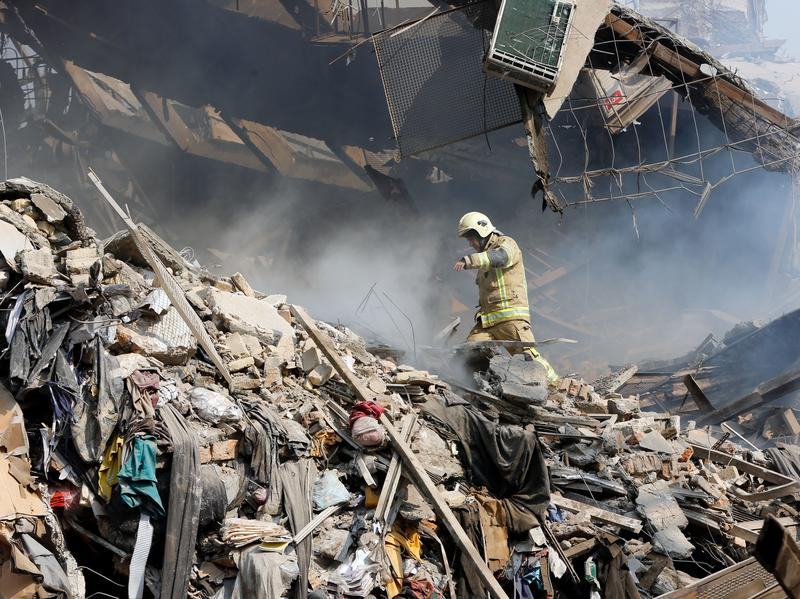 An Iranian firefighter walks amid the debris of Tehran's 17-story Plasco building after it became engulfed in flames and collapsed Thursday.
