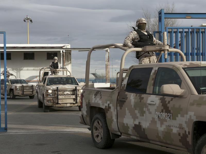 """Mexican soldiers leave the airport in Ciudad Juarez, Mexico, after authorities handed over drug lord Joaquin """"El Chapo"""" Guzman to U.S. officials."""