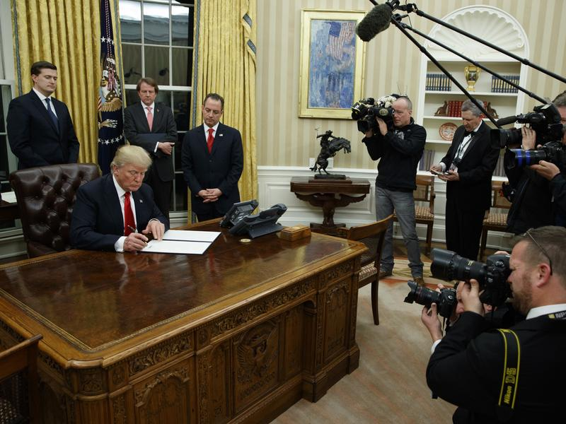 Within hours of taking the oath of office, new President Donald Trump signed his first executive order in the Oval Office while the press looked on.