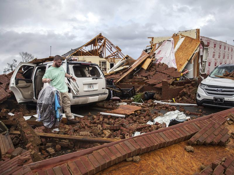 A man retrieves clothing from a damaged car parked at a home in Adel, Ga., that was hit by a tornado on Sunday.