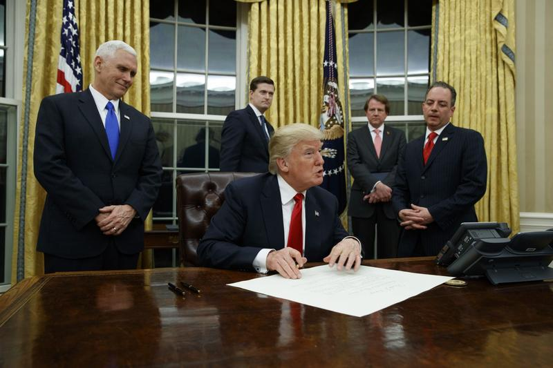 Vice President Mike Pence watches at left as President Donald Trump prepares to sign his first executive order, Friday, Jan. 20, 2017, in the Oval Office of the White House in Washington. (Evan Vucci/AP)