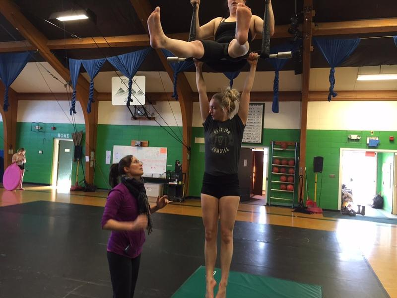 As Ringling Bros. announces it will close, New England Center for Circus Arts in Brattleboro is keeping the art of circus performing alive. The group's co-founder Elsie Smith (left) works with Cherie Jacque and Miranda Kent on the trapeze. (Howard Weiss-Tisman/VPR)