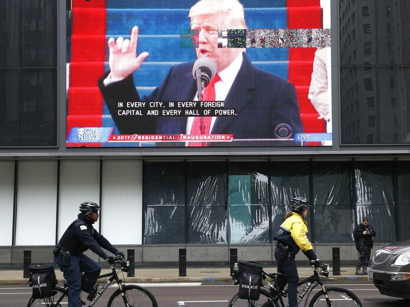 """Chicago police officials ride bikes by a broadcast of President Trump's inaugural address on Jan. 20. The president has threatened to """"send in the Feds"""" to intervene in the city's law enforcement."""