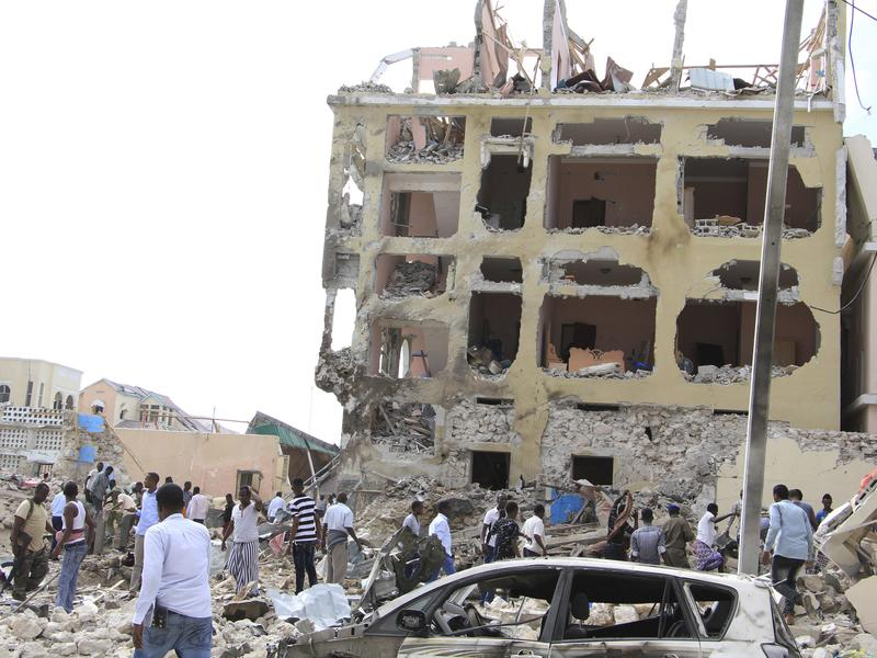 A crowd gathers near the Dayah Hotel after it was heavily damaged by bomb blasts on Wednesday in Mogadishu, Somalia.