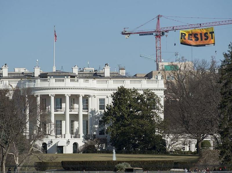 """Greenpeace protesters unfold a banner reading """"Resist"""" from atop a construction crane on Wednesday behind the White House."""