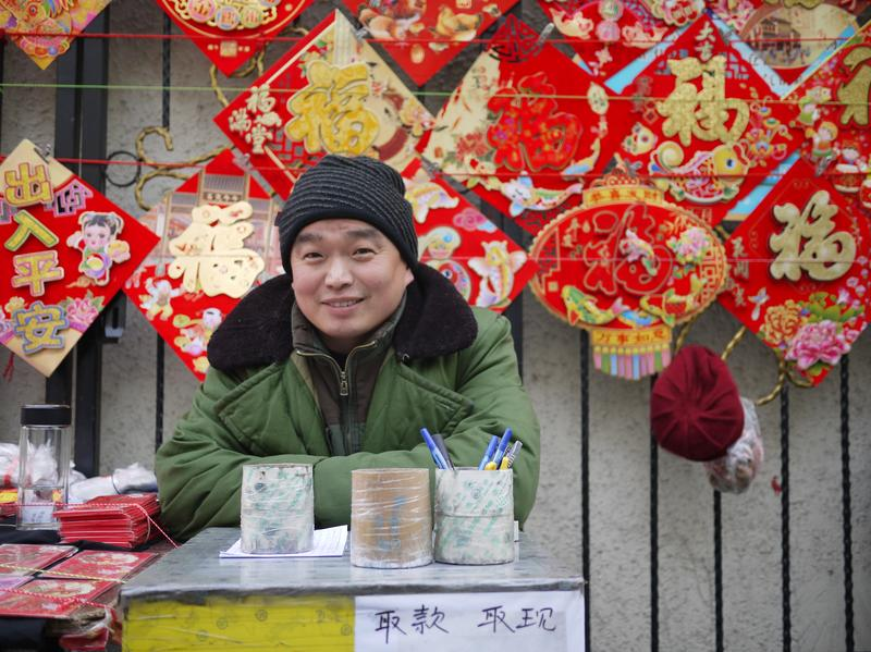 The last remaining street vendor in Rising Peace Lane before new year celebrations begin sells new year's decorations and calendars.