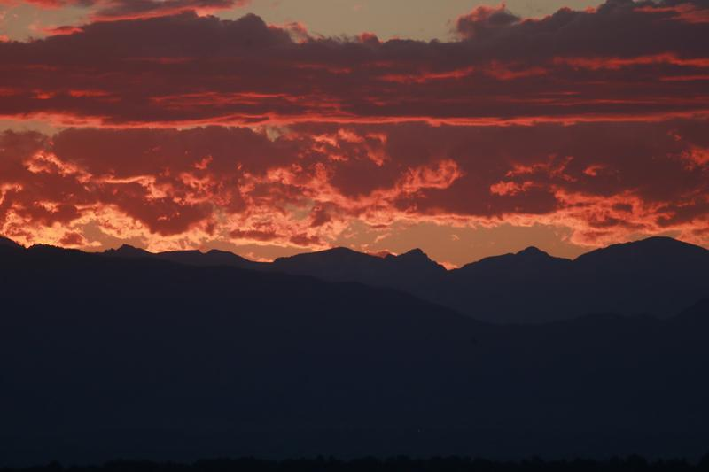 In this file photo, the sun sets behind the Rocky Mountains and a golden light illuminates the clouds late in Denver. (David Zalubowski/AP)