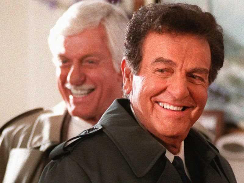 Actor Mike Connors, who starred in the TV detective show <em>Mannix</em>, flashes a smile after filming a scene with Dick Van Dyke, for an episode of <em>Diagnosis Murder</em> in 1997. The show centered around an unsolved mystery from <em>Mannix</em>, with Connors returning to his old role as the title character.