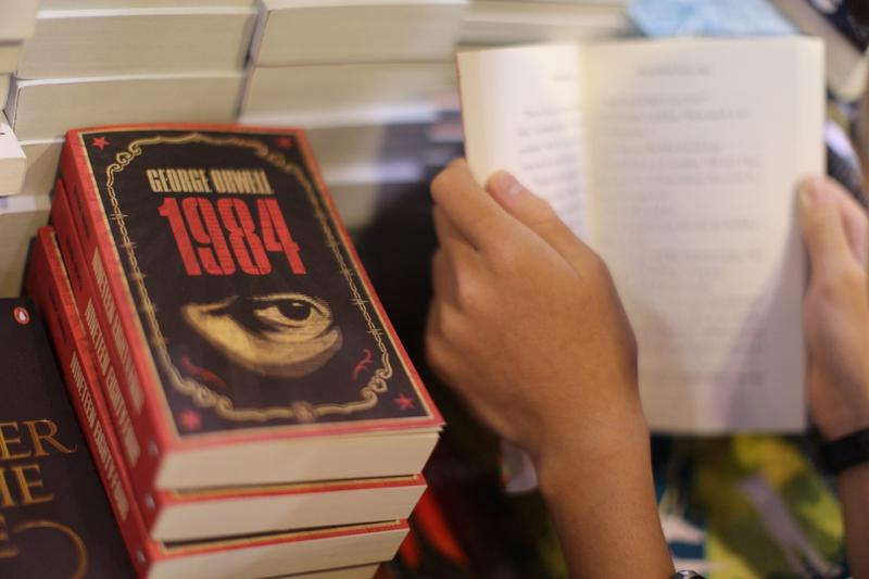 "A boy reads a book next to copies of George Orwell's ""1984"" at Hong Kong's annual book fair in July 2015. (Aaron Tam/AFP/Getty Images)"