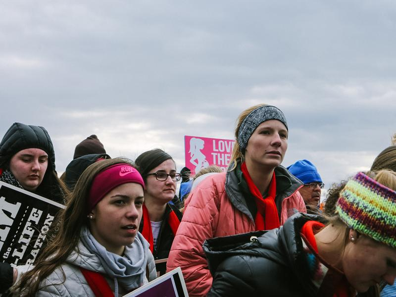 """(Left) Groups of young people travelled from around the country to listen to speakers ranging from Vice President Mike Pence to Iowa Sen. Joni Ernst ahead of the march. (Right) Towson University student Edena Zeweie, 18, came with a friend. Her friend said that they were there to be """"the voice for those who have no voice"""" and protest for Planned Parenthood to be defunded."""
