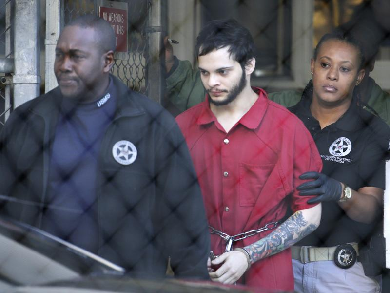 Esteban Santiago (center) is led from the Broward County jail for an arraignment in federal court on Monday in Fort Lauderdale, Fla.