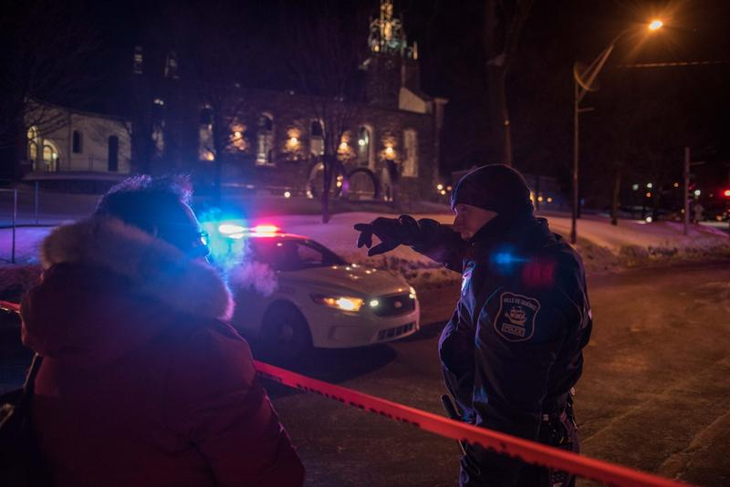 A Canadian police officer talks to a woman after a shooting in a mosque at the Quebec City Islamic cultural center on Sainte-Foy Street in Quebec City on Jan. 29, 2017. (Alice Chiche/AFP/Getty Images)