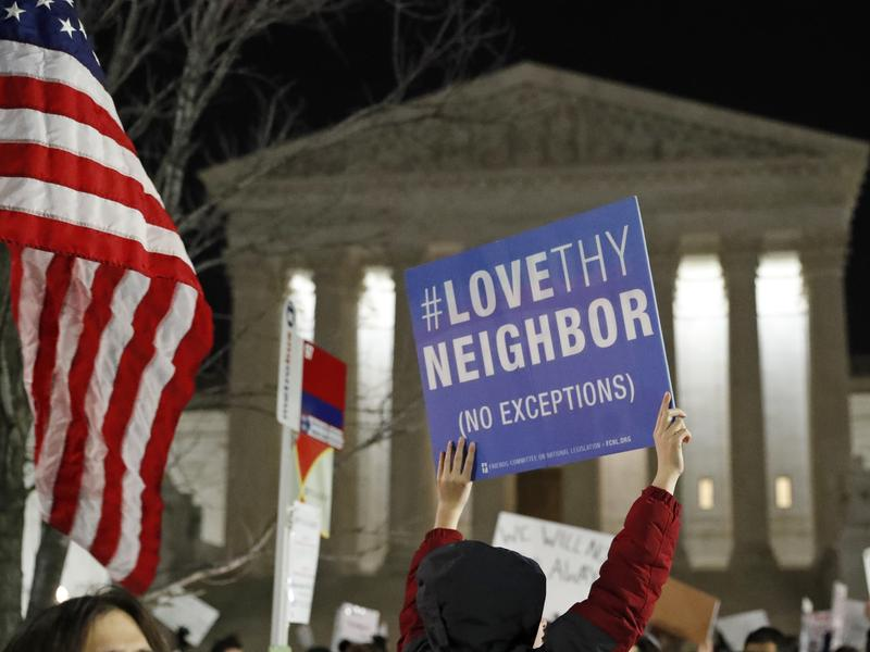 A protester carries a sign in front of the Supreme Court during a protest about President Trump's recent executive orders on Monday in Washington, D.C.