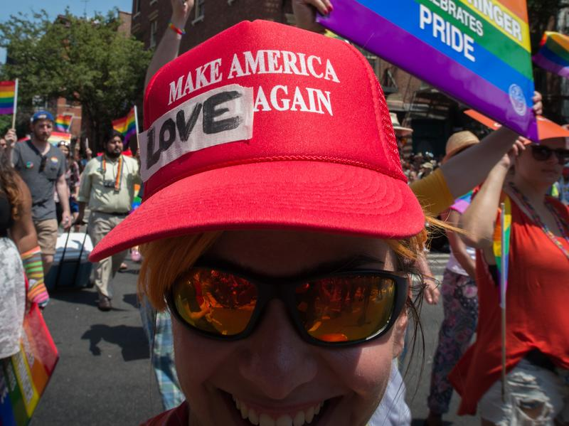 President Trump has decided to leave in place President Barack Obama's 2014 executive order protecting employees from anti-LGBTQ workplace discrimination while working for federal contractors. Here, a marcher in New York's Gay Pride march wears a modified version of a Trump campaign hat last summer.