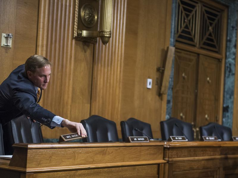 Chris Campbell, Republican staff director for the Senate Finance Committee chairman, sets nameplates out for Democratic senators who boycotted the committee vote on Rep. Tom Price, R-Ga., nominee for HHS secretary and Steve Mnuchin, nominee for Treasury secretary.