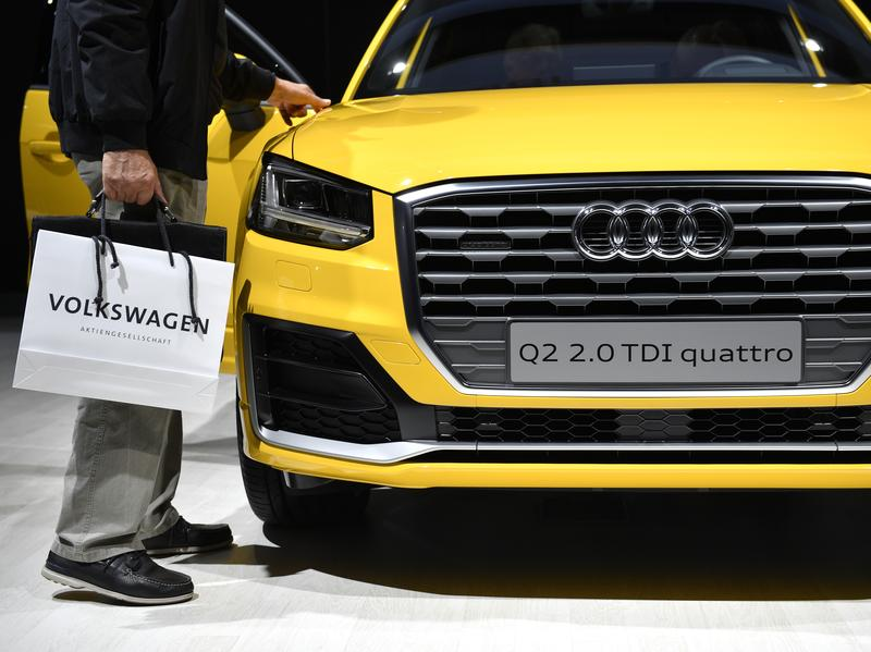 Owners of vehicles with larger VW diesel engines that have emissions-cheating software could get their cars fixed or bought back, the company says. Here, a man walks by an Audi diesel at company meetings last summer.