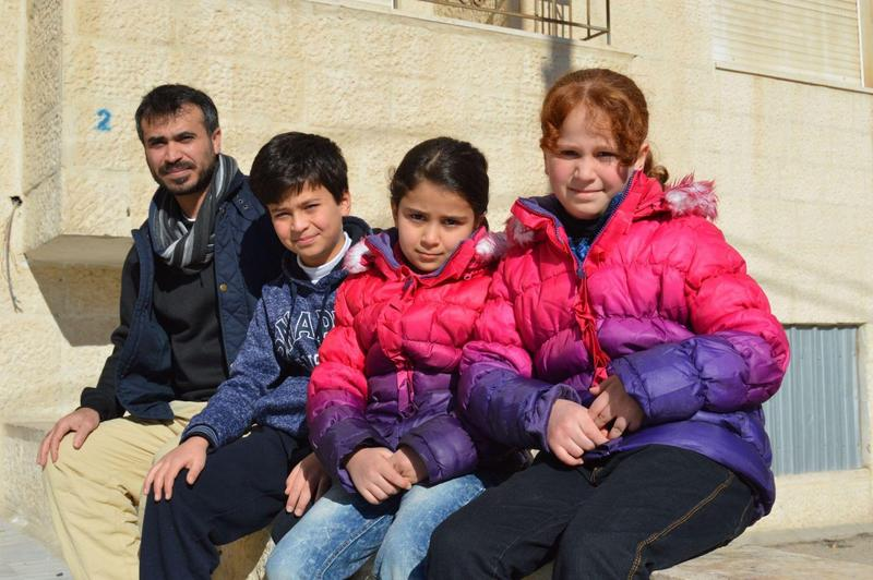 Ahmed Saa', a Syrian refugee, and his three children outside their apartment in Amman, Jordan. Saa', who has been in Jordan for four years, is among those in the city who had hoped to be resettled in the U.S. (Nina Keck/VPR)