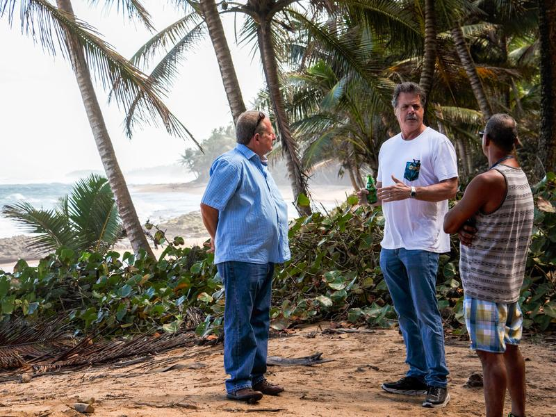 Mike McCloskey, his cousin Manuel Perez (left), and one of their co-workers on a beach at the edge of their new farm in Puerto Rico. McCloskey and Perez played on this beach as children.