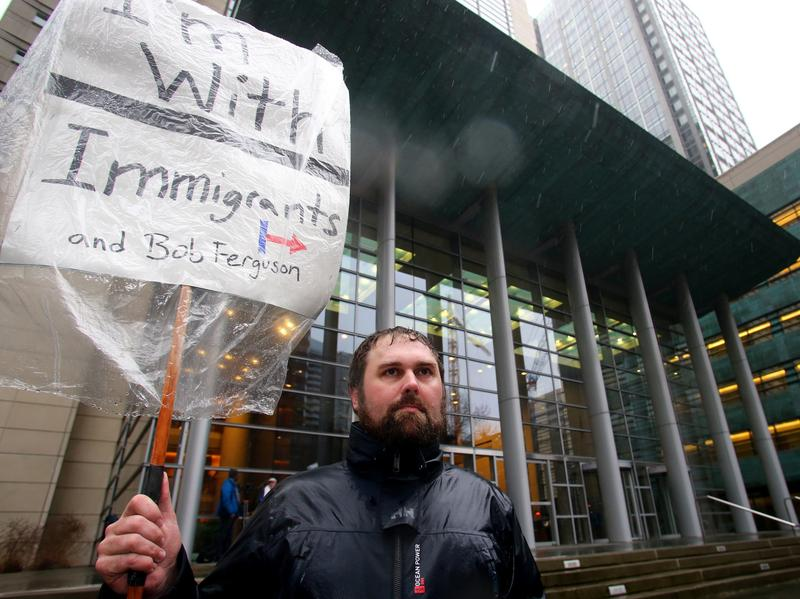 Patrick Wicklund, from Seattle, stands outside the U.S. District Court, Western Washington, on Feb. 3, 2017 in Seattle, Washington. Washington state Attorney General Bob Ferguson filed a state lawsuit challenging key sections of President Trump's immigration Executive Order as illegal and unconstitutional.